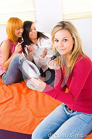 Young women applying makeup