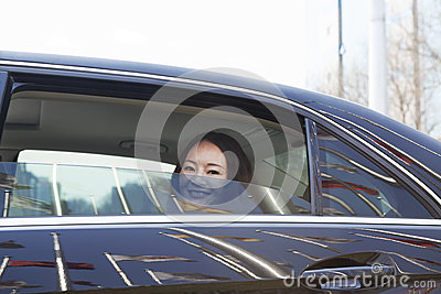 Young women in back seat of car looking out of window.