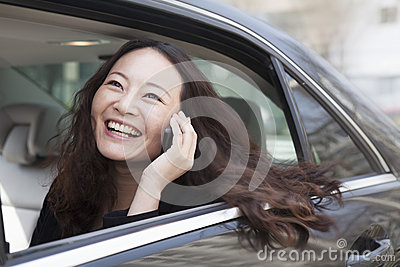 Young women in back seat of car using mobile phone.
