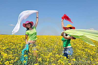 Young women on blooming rape field in summer