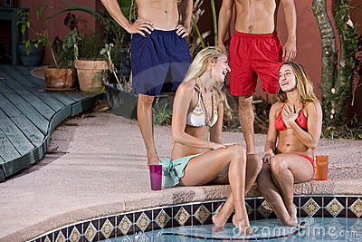 Young women chatting by pool, men standing behind