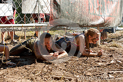 Young Women Crawl Under Electrified Fence In 5K Obstacle Race Editorial Stock Photo