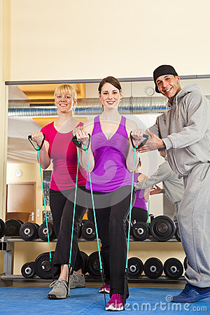Young women exercising in gym with trainer