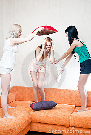 Young women fighting on pillows