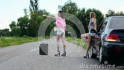 Young women hitchhiking near broken car stock video