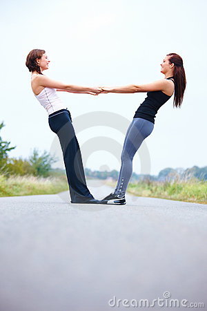 Young women holding hands on road  copyspace