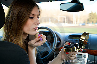 Young women preparing her make-up in car