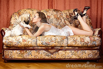 Young women with puppy on the sofa.