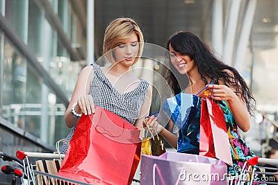 Two young fashion women with shopping bags