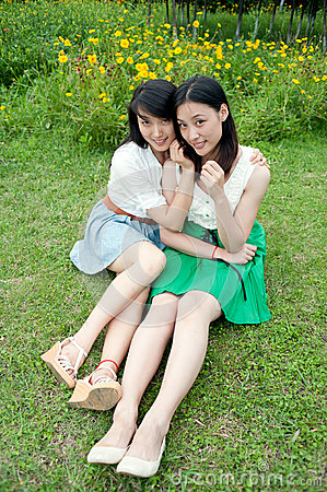 Young women sitting smiling standing on the grass
