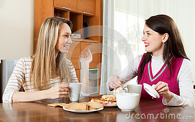 Young women table gossiping and drinking tea