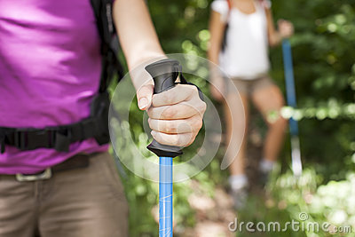 Young women trekking in forest and holding stick