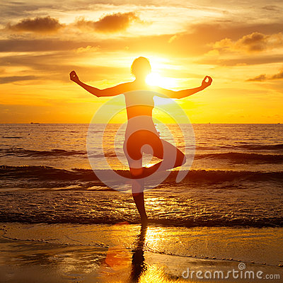Young yoga woman by the sea