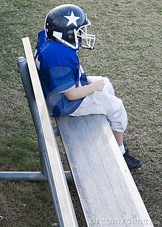 Youth football player alone on the bench