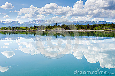 Yukon wilderness cloudscape reflected on calm lake