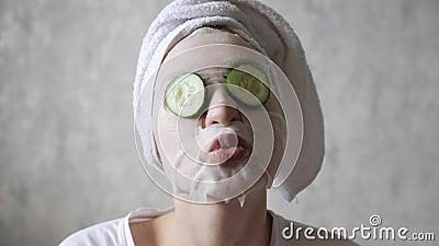 Zabawa, pielęgnacja twarzy, podnoszenie i nawodnienie Ogórki okrągłe padają z oczu młodej pięknej kobiety zbiory