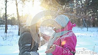 Zabawa zimowa Matka i dorosła córka trzęsąca się gałęziami jodłowymi z śniegiem na zewnątrz Śmiech rodziny zdjęcie wideo