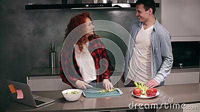 Zabawna para podczas gotowania razem w szarej kolorowej kuchni, młoda aktywna rodzina z zabawą śmieje się beztrosko zbiory