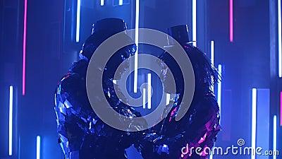 Zabawni i zabawni tancerze wstrząsają głowami w synchronicznym kostiumie, odbijając światło na neonową ścianę zdjęcie wideo