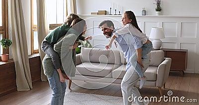 Zabawni szczęśliwi rodzice, niosący dzieci bawiące się w grę w salonie