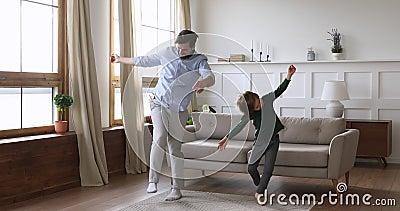 Zabawny, szalony tatuś i słodki syn bawiący się tańcząc