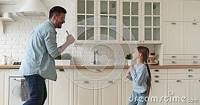 Zabawny szczęśliwy ojciec i córka śpiewają razem w kuchni zbiory
