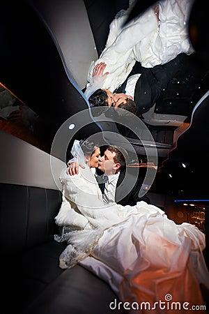 Zachte kusbruid en bruidegom in huwelijkslimo