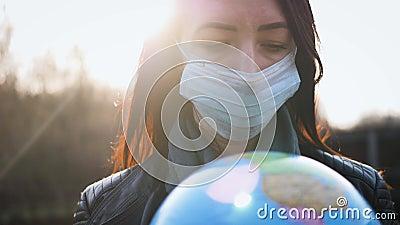 Zadde vrouw in een medisch masker, terwijl ze de aarde in de zon houdt COVID-19-concept stock footage