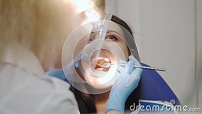 Zahnarzt, der die Z?hne eines Patienten im Zahnarztb?ro ?berpr?ft stock footage