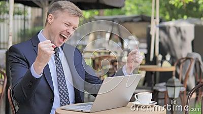 Zakenman Celebrating op Laptop in Openluchtkoffie stock footage