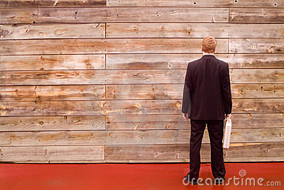 Zakenman die een muur onder ogen ziet