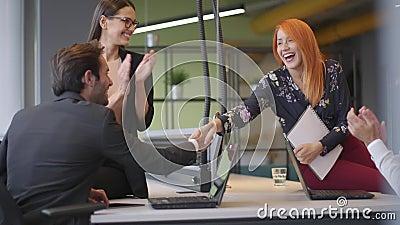 Zakenman en zakenvrouw schudden de handen in de schoot voor het concept van succes van een overeenkomst stock videobeelden