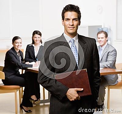 Zakenman met notitieboekje en medewerkers