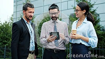 Zakenmensen die praten met een tablet buiten kantoor om zaken te bespreken stock footage
