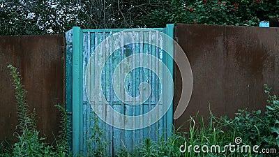 Zamknięta, zakrywający błękitna furta w ogrodzeniu w wsi, lub drzwi Zaniechana brama scena wiejskiej Bezludny miejsce zdjęcie wideo