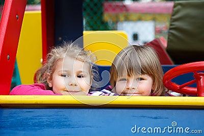 Zamyka dziewczyna twarze dwa szczęśliwych figlarnie dziewczyny