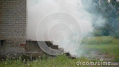 Zamykająca się biała cegła z gankiem, z którego wychodzi dym biały, niebezpieczeństwo pożarów w domach i wybuch gazu zbiory