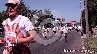 Zaporizhzhia Ukraina - April 29, 2018: Maratonlöpare i en vit T-tröja och svarta kortslutningar, i gröna lock och arkivfilmer