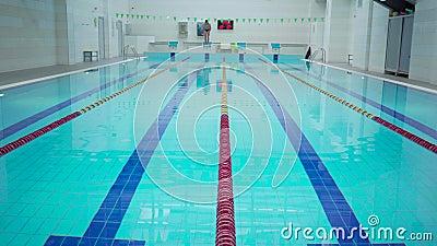 Zawodowy pływak sportowy ledwo pracuje w pustych pomieszczeniach skacząc i pływając po torze zbiory