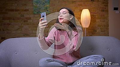 Zbliżenie krótkopęd młodej ładnej brunetki caucasian kobieta ma wideo wzywa uśmiechniętego obsiadanie na i telefon zbiory