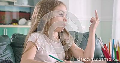 Zbliżenie smutnej kaukaskiej dziewczynki liczącej na palce i piszącej wyniki do książki ćwiczeń Sprytne dziecko zbiory