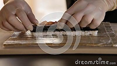 Zbliżenie Sushi Chef Hands umieszcza wędzone węgorz na liściu nori i mięsie kraba Proces produkcji sushi Rolls the sushi roll zbiory