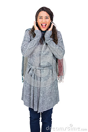 Zdziwiona brunetka jest ubranym zimę odziewa pozować