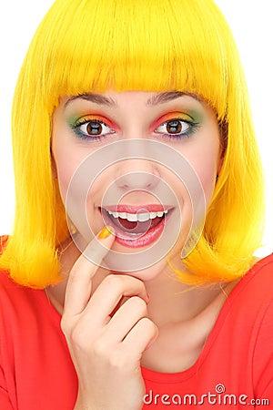 Zdziwiona kobieta jest ubranym żółtą perukę