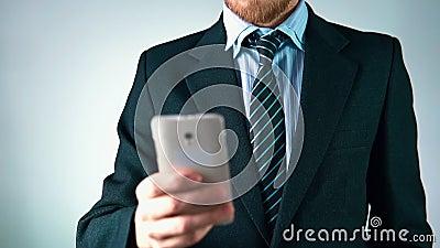 Zeitlupe, ein stilvoller Mann in einer Klage benutzt einen Handy schaut elegant stock video footage