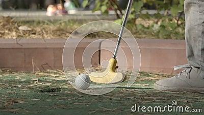 ZEITLUPE: Kleiner Spieler schlägt einen Golfball, um Kurs zu durchlöchern stock footage
