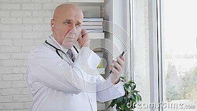 Zeitlupe mit Doktor in der medizinischen Kabinettsbildung ein Telefon-Anruf unter Verwendung der Hände frei stock footage