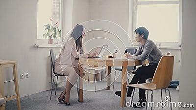 Zekere Europese vrouwelijke advocaat die aan de jonge Japanse mens door de lijst spreken Multi-etnische bespreking in modern bure stock videobeelden
