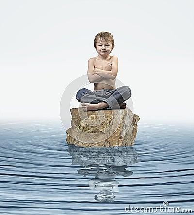 Zen Kid on rock in water