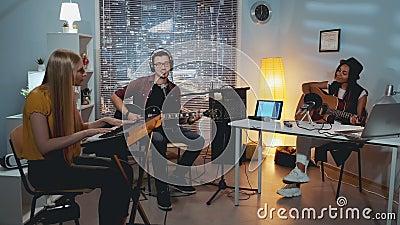 Zespół muzyczny młodych ludzi z różnych ras nagrywających nowy utwór w studiu domowym zdjęcie wideo